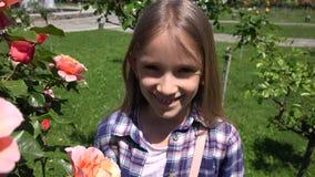 儿童画象微笑室外在公园由玫瑰丛,笑的女孩面孔4K