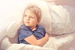 儿童病残在与热病和温度计的床上 免版税图库摄影