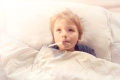 儿童病残在与热病和温度计的床上 免版税库存照片