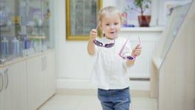 儿童白肤金发的女孩跳舞和尝试五颜六色的玻璃在医疗商店-在诊所的购物 影视素材