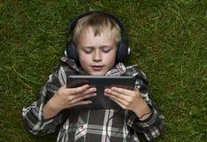 儿童白肤金发的年轻男孩画象使用与一台数字式片剂计算机的户外说谎在草 免版税图库摄影