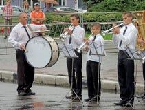 儿童的军乐队拍打表现在雨中 免版税库存照片