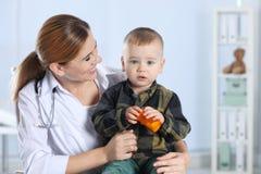 儿童的医生与一点患者一起使用在医院 免版税库存图片