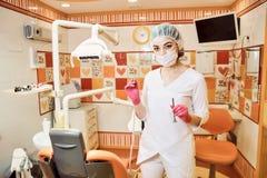 儿童的医生牙医女孩在拿着工具的牙齿办公室 免版税库存图片