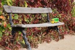 儿童的在公园长椅的玩具卡车 库存图片