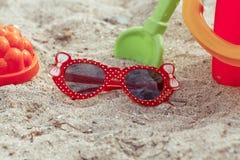 儿童的太阳镜和玩具在沙子的一个海滩说谎 减速火箭的猪圈 免版税库存图片