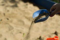 儿童的手倾吐与一把蓝色铁锹的沙子 免版税库存照片