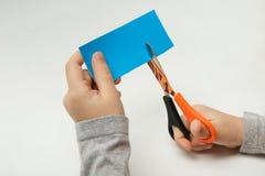 儿童的手剪蓝纸小条在白色背景的 库存照片