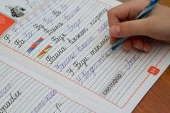 儿童的手在笔记本写 库存图片