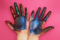 儿童的手弄脏与在桃红色背景的多彩多姿的油漆 免版税库存图片