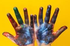 儿童的手弄脏与在黄色背景的多彩多姿的油漆 免版税图库摄影
