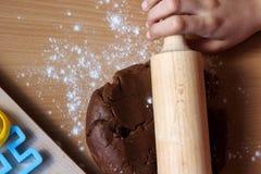 女孩覆盖的面团的手与滚针的 烹调传统复活节饼干 复活节食物概念 图库摄影