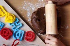 女孩覆盖的面团的手与滚针的 烹调传统复活节饼干 复活节食物概念 库存图片