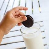 儿童的手用OREO饼延伸到牛奶 免版税图库摄影