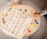 儿童的木字母表在桌上说谎在孩子旁边 库存照片