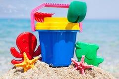 儿童的桶、锹和其他玩具在热带海滩反对b 库存照片