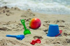 儿童的沙盒的玩具飞机反对海和海滩 免版税库存照片