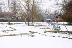 儿童的游乐场在雪下的冬天 摇摆、转盘和幻灯片 冬天荒芜 免版税库存图片