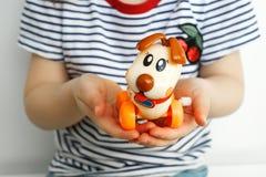 儿童的玩具狗在孩子的手上 库存图片