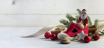 儿童的红色鞋子用甜点和圣诞节装饰f填装了 免版税库存图片