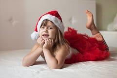 儿童的脚在对床的新年的镶边的睡衣末端, 免版税库存照片