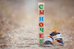 儿童的鞋子和词儿子 库存照片