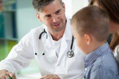 儿童的医生和他的患者 免版税库存照片