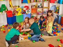儿童积木在幼儿园 演奏玩具地板的小组孩子 库存图片