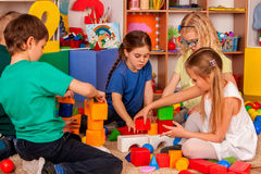 儿童积木在幼儿园 演奏玩具地板的小组孩子 免版税库存照片