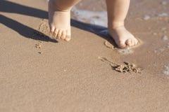 儿童立场的腿在海滩的 在沙子的婴孩脚 背景球海滩美好的空的夏天排球 夏令时假日概念 复制空间 库存图片