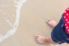 儿童立场的腿在海滩的 免版税库存照片