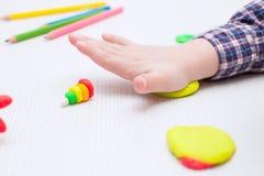 儿童繁忙使用与在一张白色桌上的彩色塑泥 图库摄影