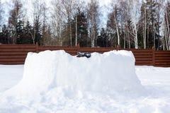 儿童腿黏附在雪堡垒外面墙壁  库存图片