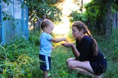 儿童自然发现 孩子在手中投掷母亲五谷  孩子和母亲的照片,由后照 免版税库存图片
