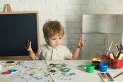 儿童艺术 愉快的绘画 孩子为学校做准备 有油漆的男孩 免版税库存图片