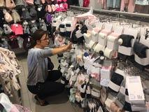 儿童衣裳的妇女购物 免版税库存图片