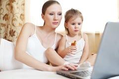 儿童计算机怀孕膝上型计算机的母亲 库存照片