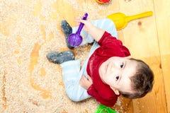 儿童谷物在地板和使用上驱散了 免版税库存图片