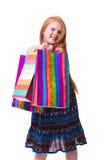 儿童购物。 愉快的方式有购物的一点红头发人女孩 免版税库存照片
