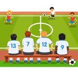 儿童足球队员坐长凳 免版税库存照片