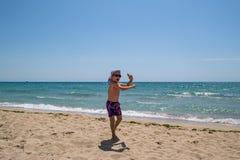 儿童跳舞和跳跃在海滩 库存照片