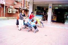 儿童车推进深圳的瓷母亲三个年轻人 库存照片