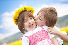 儿童逗人喜爱的亲吻的年轻人 免版税库存照片