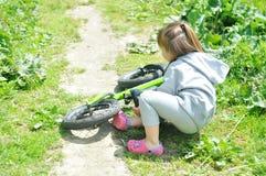 儿童逗人喜爱的小女孩跌下她的自行车在森林里 免版税库存图片