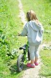 儿童逗人喜爱的小女孩骑马自行车在森林里 图库摄影
