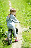 儿童逗人喜爱的小女孩骑马自行车在森林里 免版税库存照片