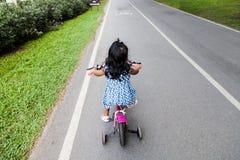儿童逗人喜爱的小女孩骑马自行车 免版税库存图片