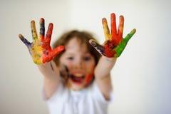 儿童面孔和手在油漆,他笑 图库摄影
