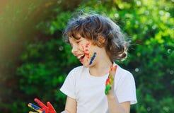 儿童面孔和手在油漆 免版税库存照片