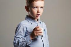 儿童饮用奶 小微笑的男孩享用牛奶鸡尾酒 健康寿命 库存照片